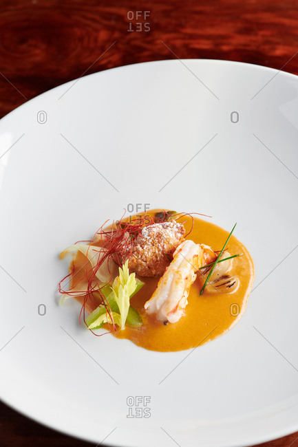 Top down view of gastronomy style dish of Kauai white shrimp with seafood broth puree and raw celery, chili threads, onion and other small flavor components served