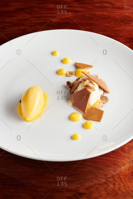 Gastronomy style dessert of lemon cream, vanilla, toffee and chocolate