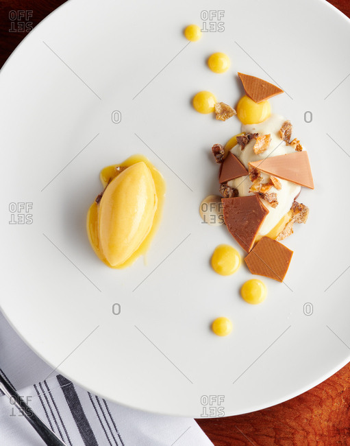 Top down view of gastronomy style dessert of lemon cream, vanilla, toffee and chocolate