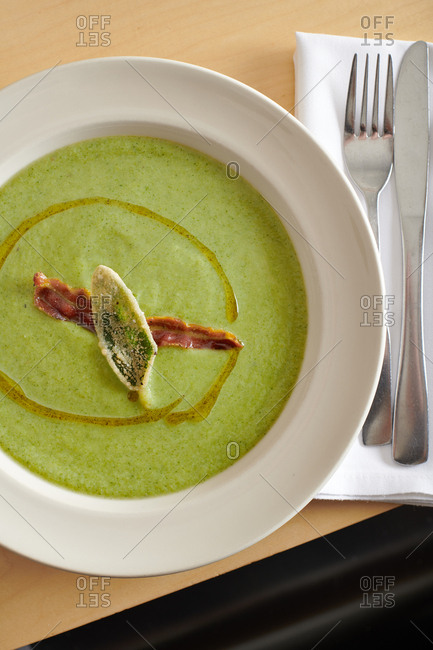 Pureed soup of broccoli and cream garnished with a fired sage leaf, bacon strip and drizzle of olive oil