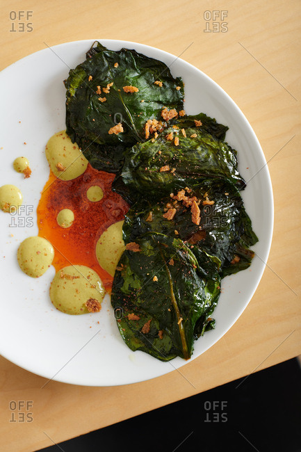 Top down view of spinach wrapped BBQ duck wing with chili oil