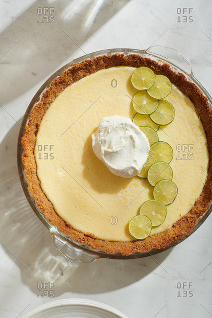 Overhead view of Key Lime Pie with key lime slices and dollop of whipped cream