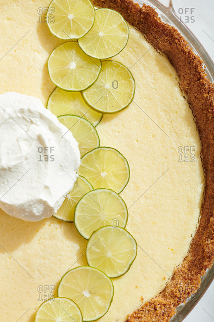 Close up of section of Key Lime Pie with key lime slices and dollop of whipped cream