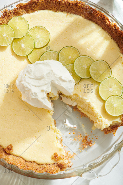 Close up of Key Lime Pie with key lime slices and dollop of whipped cream with ragged slice missing