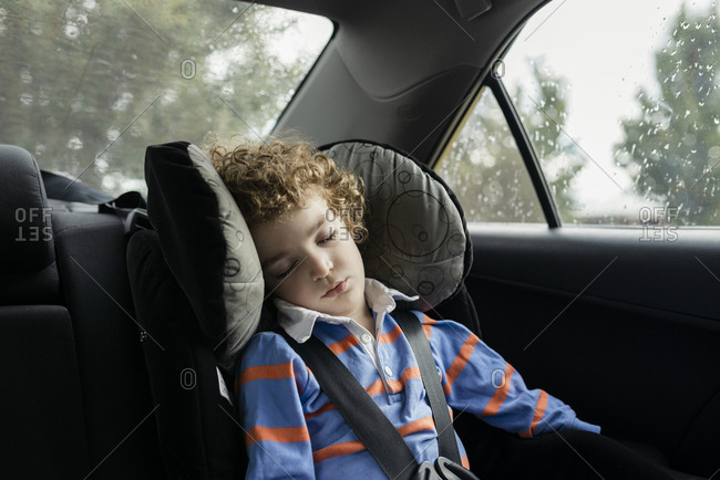 Little boy napping in car seat on car journey
