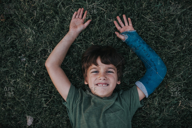 Young boy with cast on his arm laying on back on grass