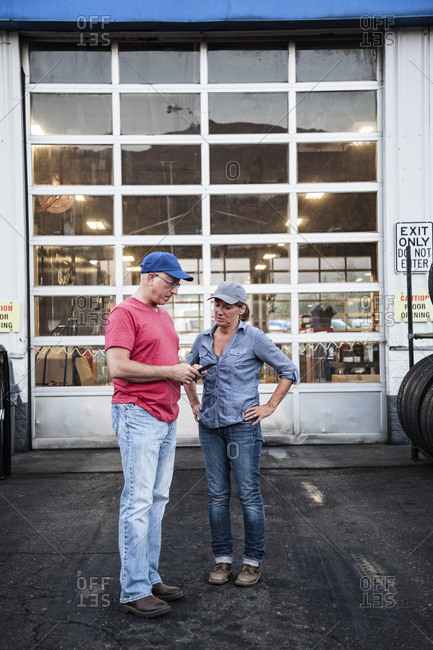 Caucasian man and woman truck drivers in front of an entrance bay at a truck stop service center