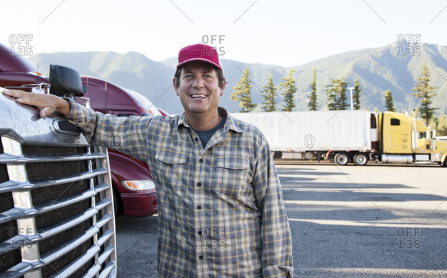 Caucasian man truck driver with his truck parked in a lot at a truck stop