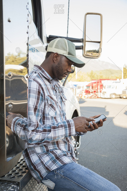 Black man truck driver texting while standing next to his truck cab parked in a lot at a truck stop