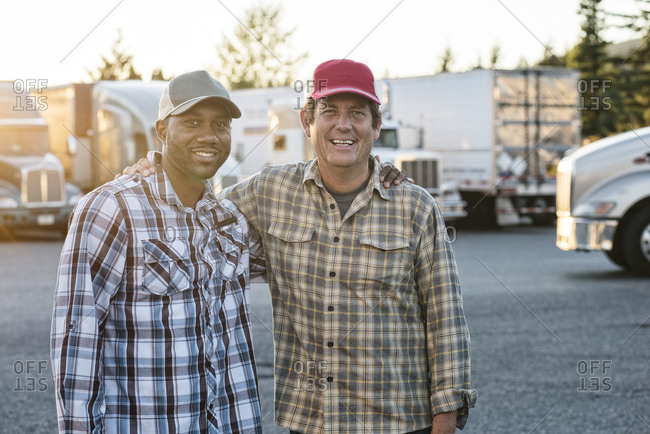 A Caucasian man and a black man truck driving team together in a truck stop parking lot