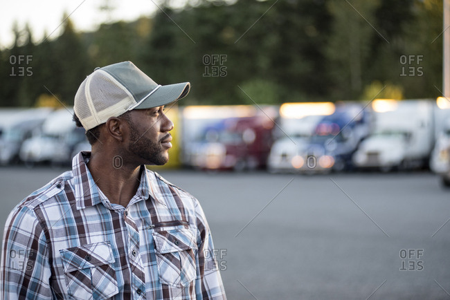 Black man truck driver near his truck parked in a parking lot at a truck stop