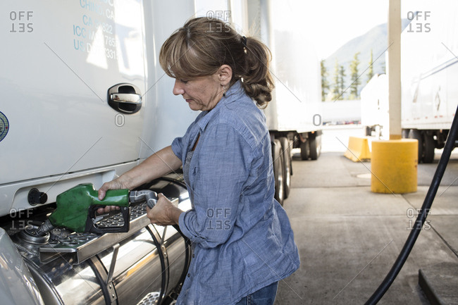 Caucasian woman truck driver filling truck with diesel fuel at a truck stop