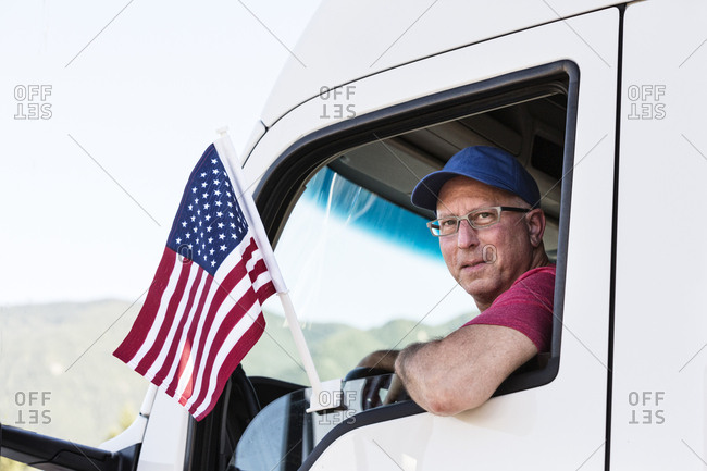 Caucasian man truck driver in the cab of his truck with an American Flag attached to the window