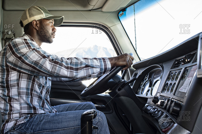 Black man truck driver in the cab of his commercial truck