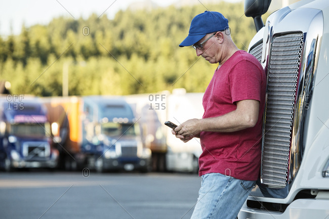 Caucasian man truck driver texting while standing next to the grill of his commercial truck in a struck stop