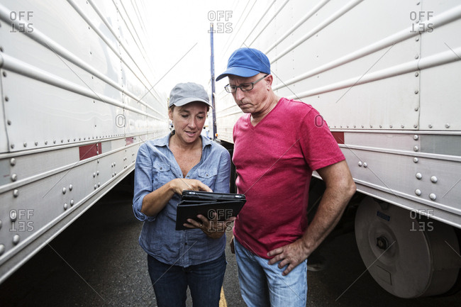 Caucasian man and woman truck driving team going over data on a cell phone while standing between trucks at a truck stop