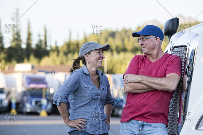 Caucasian man and woman driving team talking in front of a large truck at a truck stop