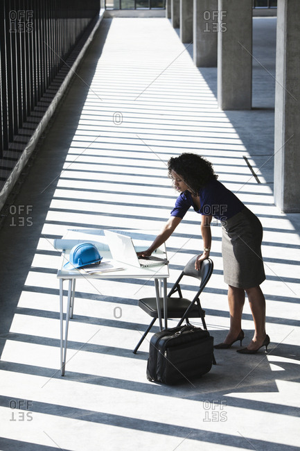 Black businesswoman working on a computer at a desk in a large empty office space