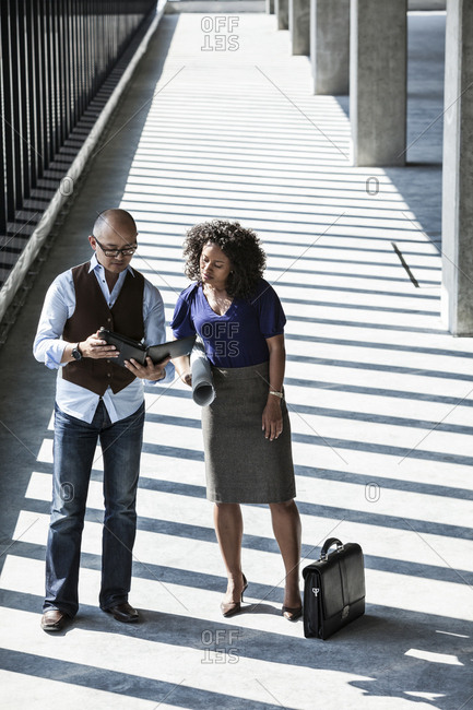 Asian businessman and black businesswoman in a large empty office space lit by the afternoon sun