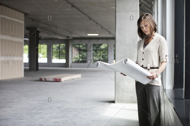 Caucasian businesswoman going over plans for a new office in a large empty raw office space