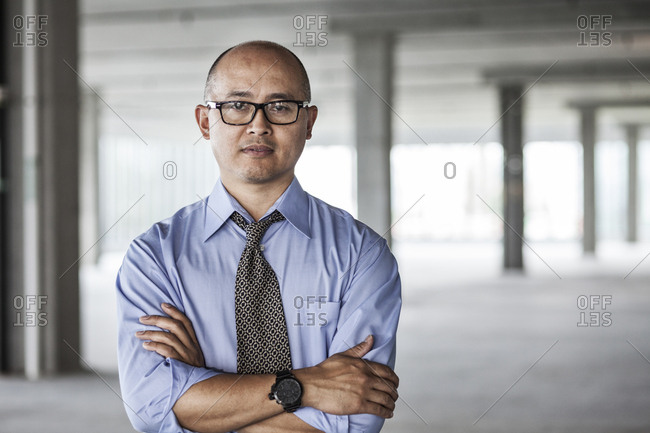 Asian businessman taking a look at a large empty raw office space