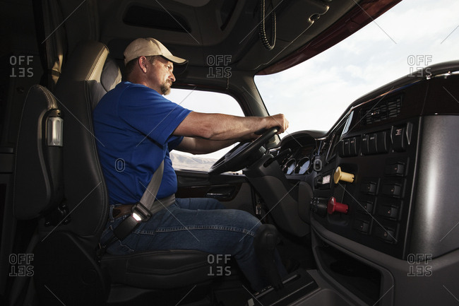Caucasian man driver in the cab of a  commercial truck