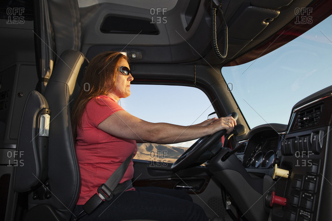 Interior cab view of a Caucasian woman driver driving her  commercial truck