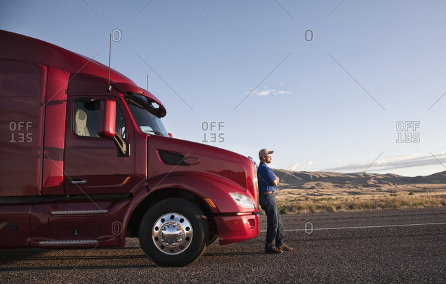 Truck driver leaning on the grill of his  commercial truck