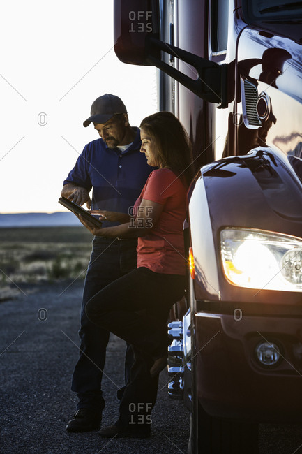 Husband and wife driving team checking their notebook computer log while standing next to the cab of their  commercial truck after sunset