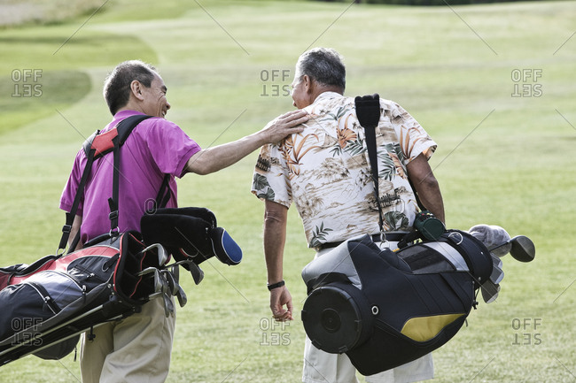 Two senior friends golfing and walking on a fairway toward their next shots