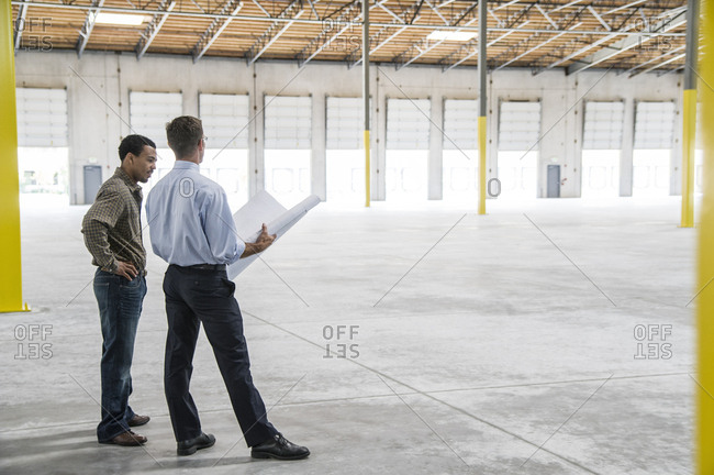 Back man owner of new warehouse and Caucasian man architect going over blue print plans of new interior layout
