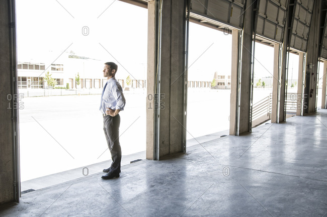 Caucasian man in shirt and tie standing in loading dock door of new empty warehouse anticipating the arrival of the first truck load new business