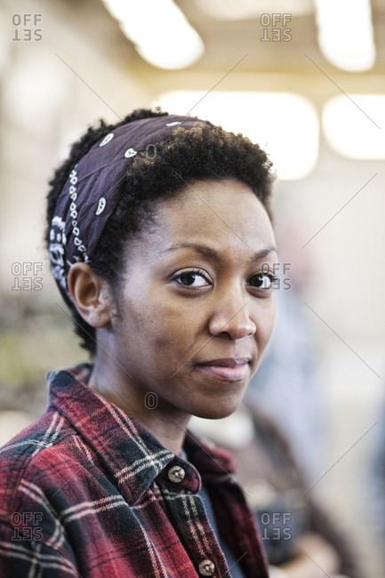 Black woman wearing a bandana in a factory