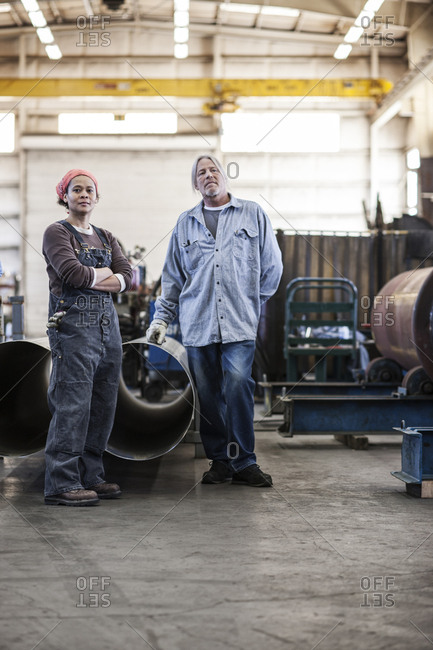 Black woman and Caucasian male workers in a sheet metal factory