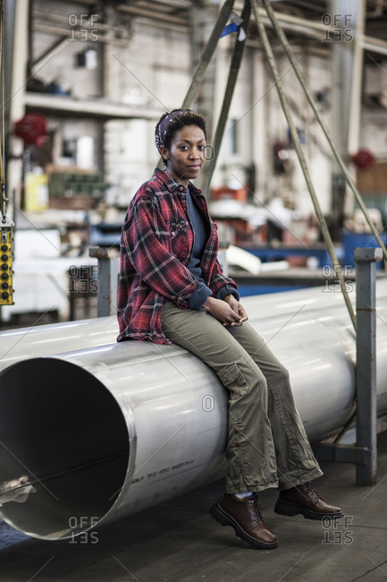 Black woman sitting next to a lift with aluminum pipes in a sheet metal factory