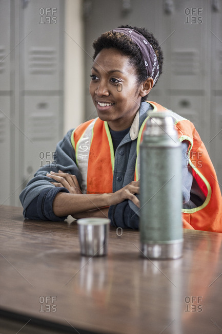 Black woman factory worker wearing a safety vest and  taking a break in a factory break room