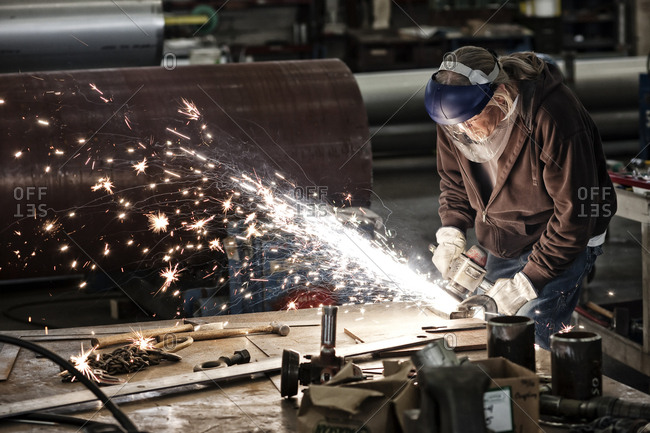 Factory worker grinding a steel edge in a sheet metal factory