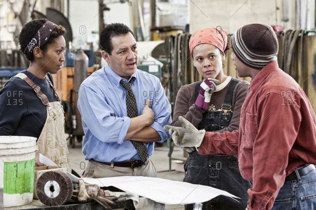 Mixed race team of workers and Hispanic man manager talking over an issue in a sheet metal factory