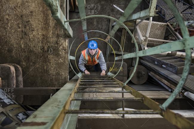 Factory worker climbing up a ladder in a sheet metal factory