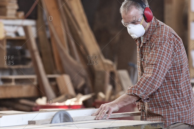 Caucasian man factory worker wearing hearing protection and a nose dust mask while cutting wood on a table saw