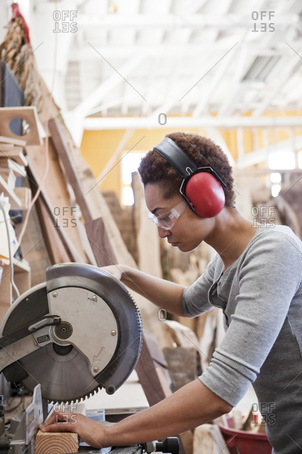 Black woman factory worker using a radial saw to cut wood in a woodworking factory
