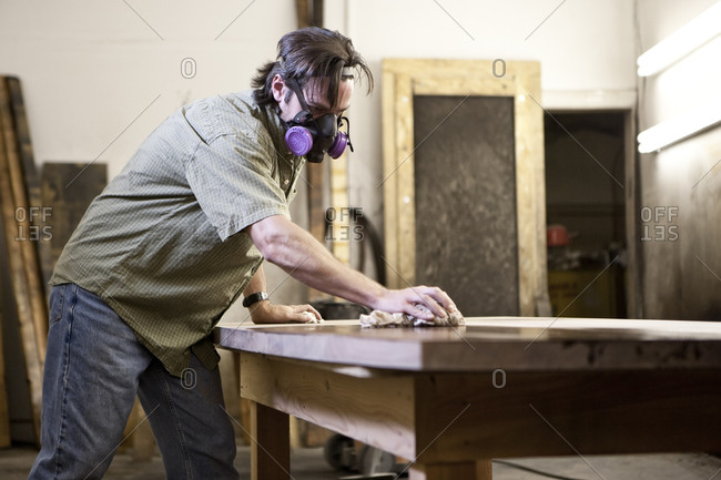 Caucasian man factory worker applying finish stain to the top of a table in a woodworking factory