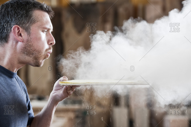 Caucasian man factory worker blowing sanding dust off a wooden piece in a woodworking factory