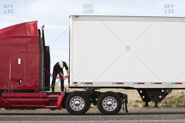 View of a driver connecting the power cables to trailer of a  commercial truck