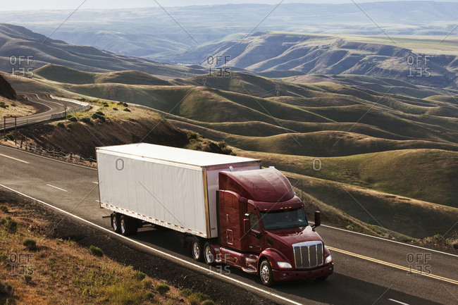 Commercial truck driving through the high rolling hills of south-eastern Washington, USA