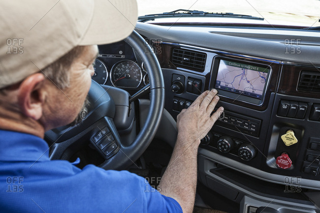 Driver parked by the side of the road using a GPS mapping device in the cab of a  commercial truck