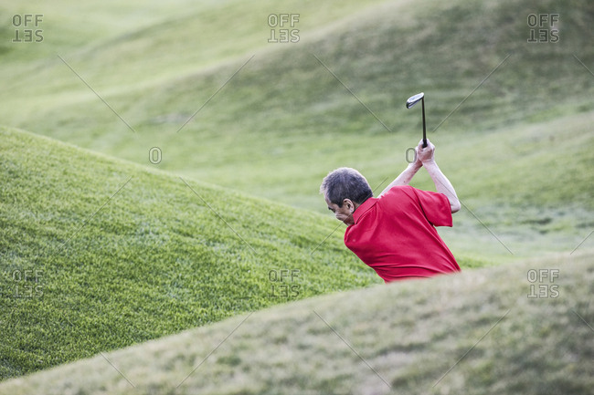 Senior golfer hitting a second shot from the fairway of a golf course