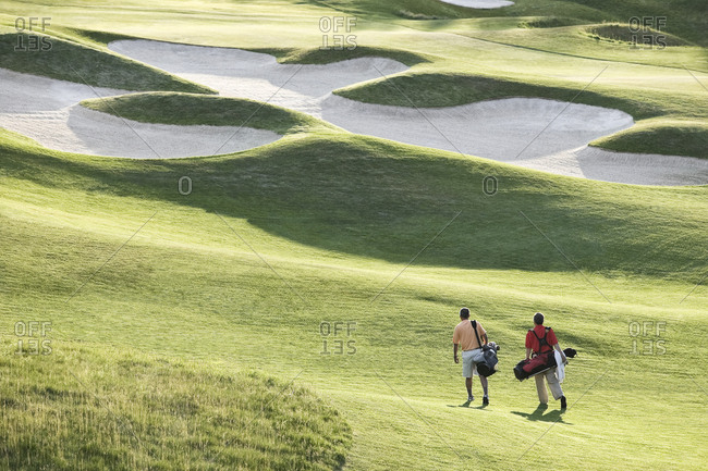 View from above of two golfers walking on a fairway toward the green of a golf course