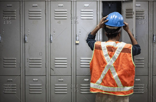 Factory worker wearing a safety vest getting ready for work next to locker in the break room