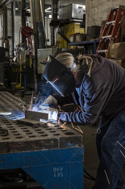 Factory worker using Oxyacetylene gas to weld two piece of metal in a sheet metal factory